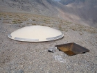 A weather station of some kind sits on the saddle between Wet Peak and South Wet Peak. The disk is about 7' in diameter.